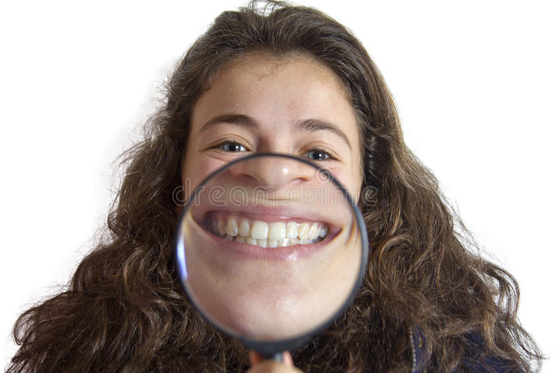 Girl smiling and show teeth through a magnifying glass royalty free stock images