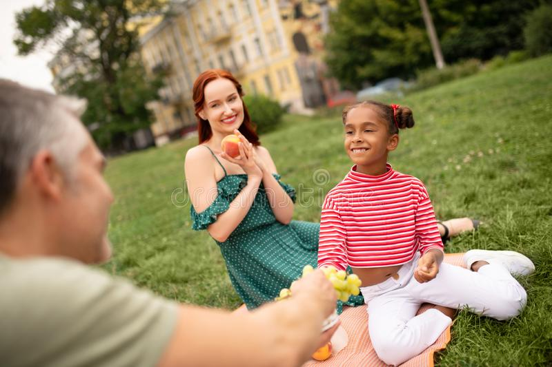 Girl smiling while taking grapes and having family picnic. Girl smiling. Girl wearing striped shirt smiling while taking grapes and having family picnic stock photography