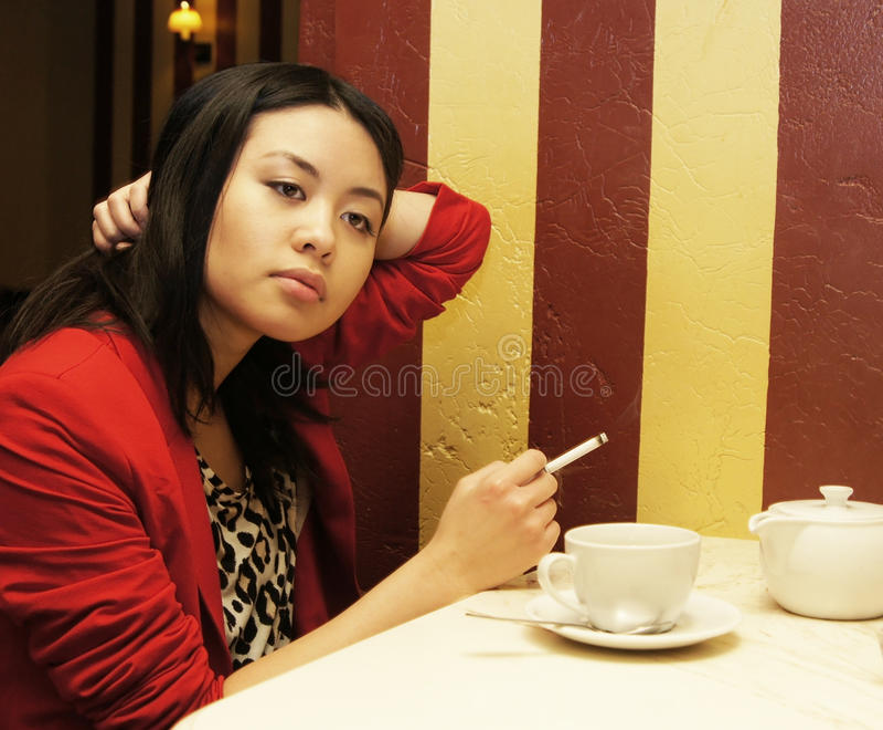 Girl smokes a cigaret. The nice Asian girl smokes a cigaret and drinks coffee royalty free stock photos