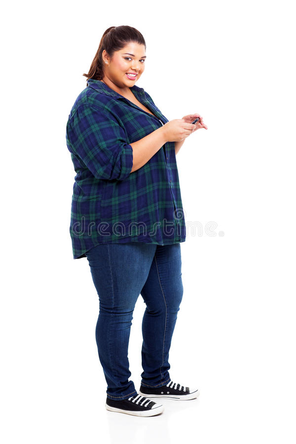 Girl sms. Attractive young large teenage girl sms on her cell phone on white background royalty free stock photos