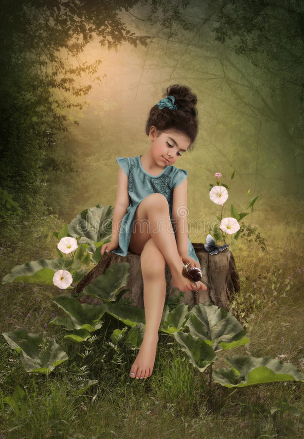 Girl and snail. The little girl in the woods sitting on a tree stump, surrounded by white flowers and burdock, and looks at the snail on his leg royalty free stock photos