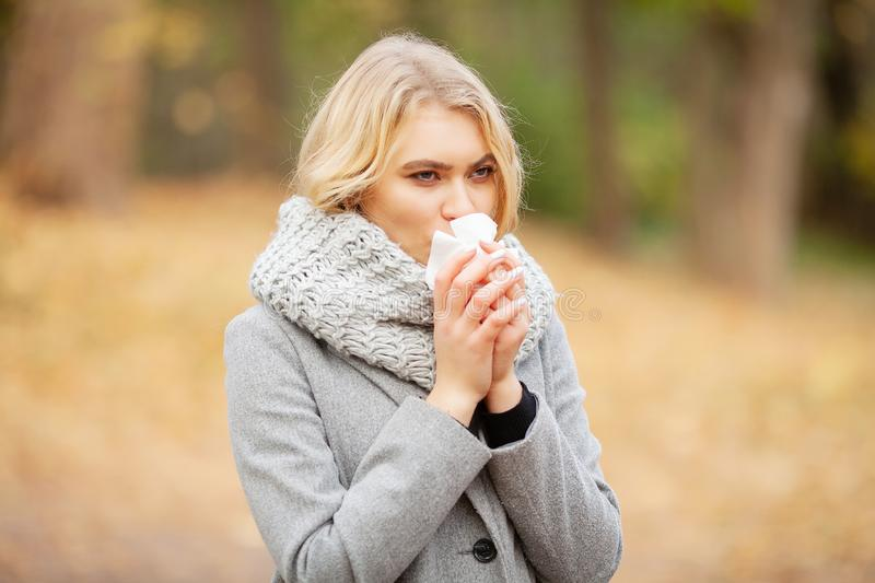 Girl sneezing in tissue. Young woman blowing her nose on the park. Woman portrait outdoor sneezing because cold and flu.  stock photos