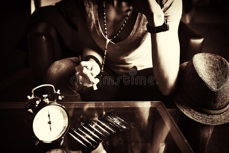 Girl sniffing cocaine with mirrored table stock photo