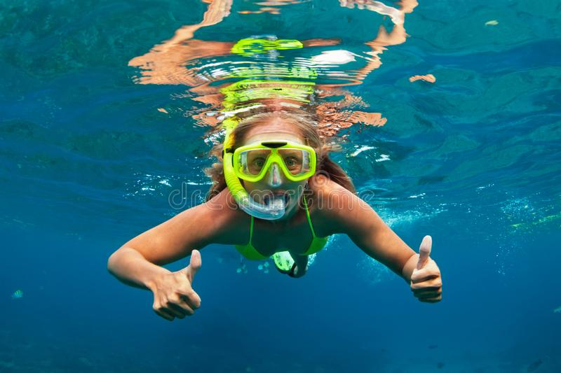Girl in snorkeling mask dive underwater with coral reef fishes stock photography