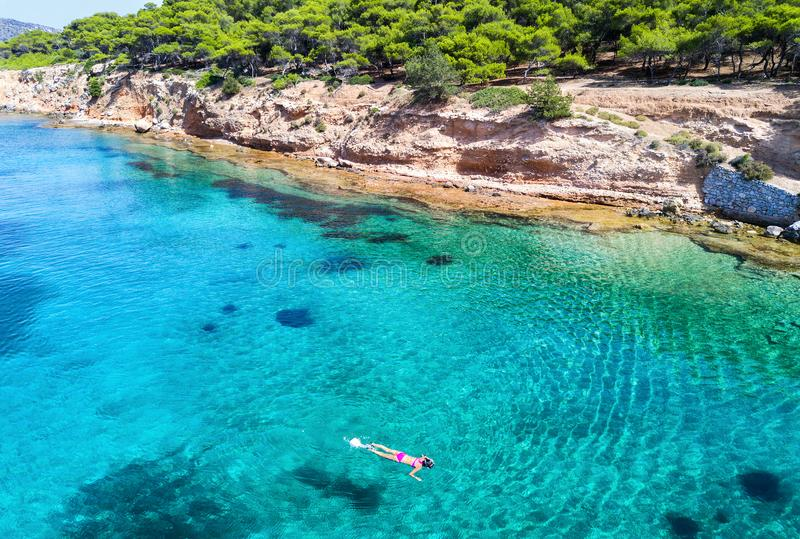 Girl snorkeling in the turquoise waters of Moni Island. Next to Aegina Island in Greece royalty free stock images