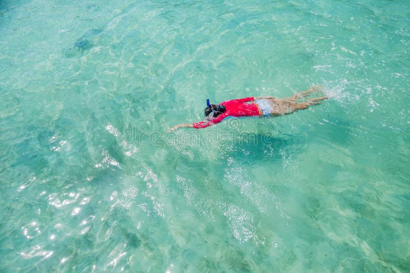 Girl snorkeling in the water of sea royalty free stock photography