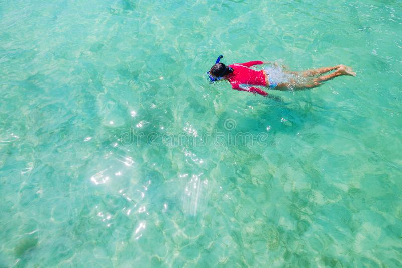 Girl snorkeling in the water of sea stock image