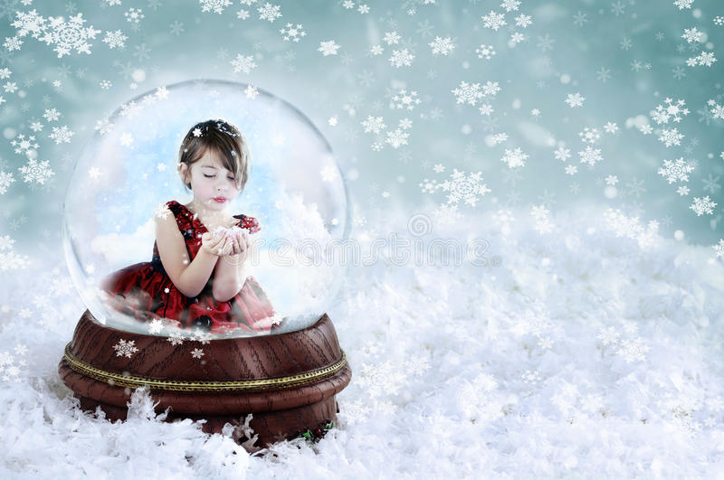 Girl in Snow Globe. Little girl inside a snow globe blowing snow out of her hands. Copy space available stock photo