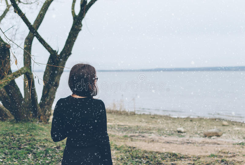 Girl And Snow. Girl on the lake and first snow in december stock photo