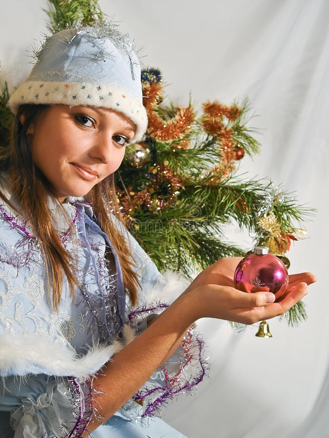 Girl Snow Maiden is decorated Christmas tree. Portrait of a beautiful brown-eyed Maiden stock image