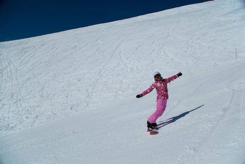 Girl on snowboard. The girl on a snowboard at mountain top on a background of white snow stock photo