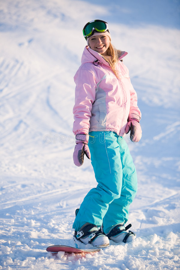 Girl on snowboard. Image of happy girl on winter resort snowboarding there stock photography