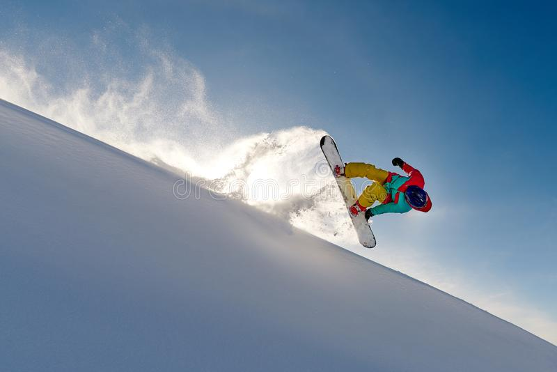 Girl snowboarder jumping front flip leaving a wave of snow royalty free stock photos
