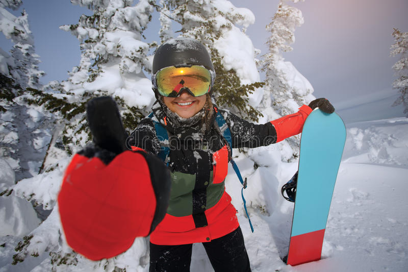 Girl snowboarder shows thumb. Positive image of winter recreation stock photos