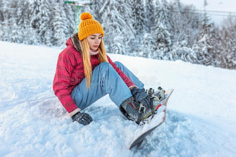 Girl snowboarder sitting alone in the snow on hill mountain outdoor, winter sport activity, equipment injury pain royalty free stock images