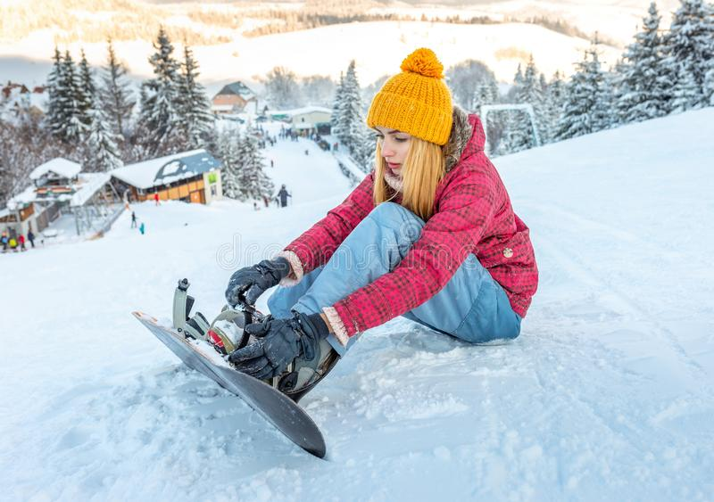 Girl snowboarder sitting alone in the snow hill mountain outdoor, winter sport activity, equipment injury a pain stock photo