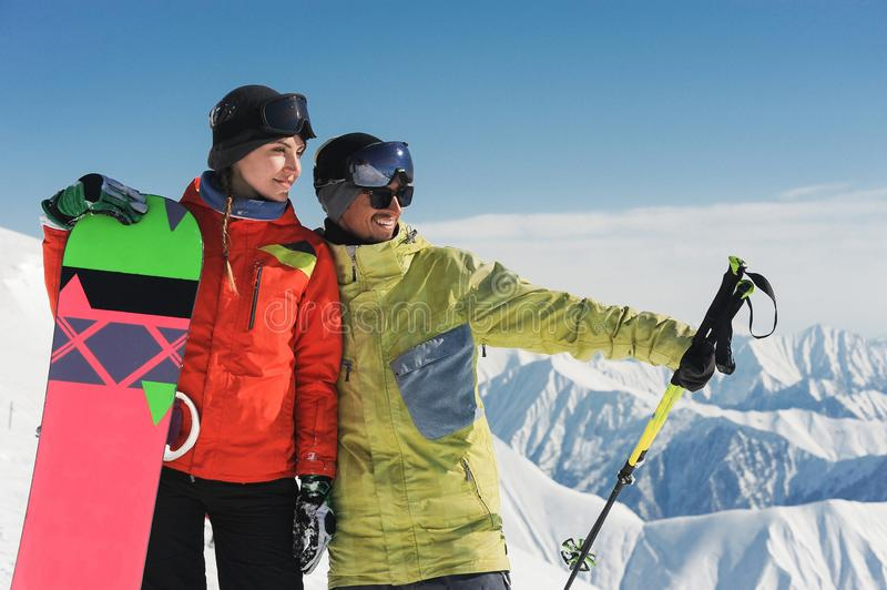 Girl snowboarder and skier enjoing the snow scenery of mountains royalty free stock image
