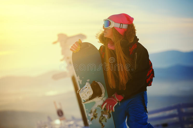 Girl snowboarding in the mountains stock images