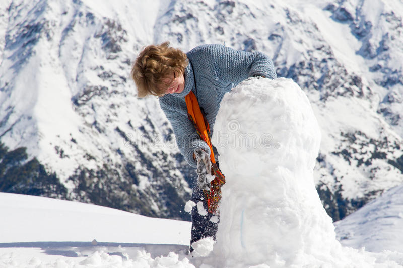 Girl snowman mountains royalty free stock image