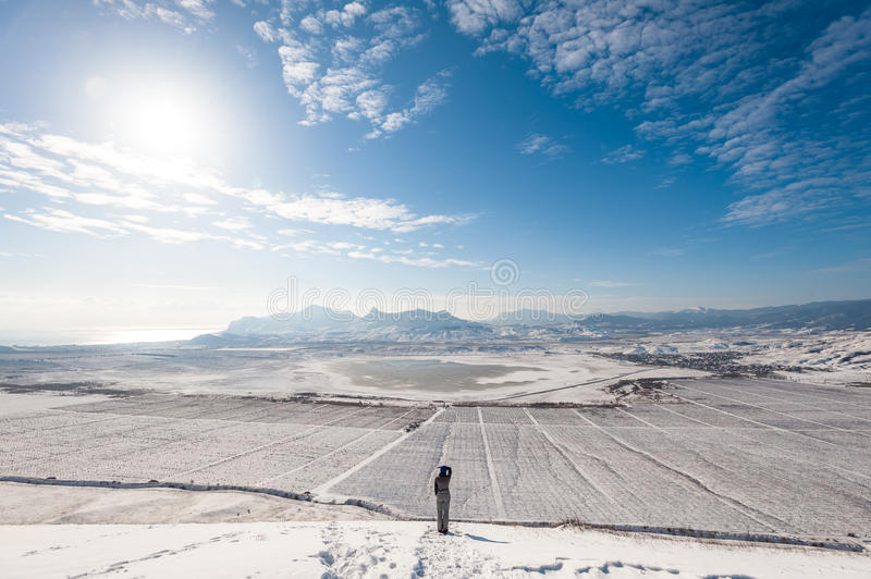 Girl on the snowy slope with mountains and the sea on background. royalty free stock image