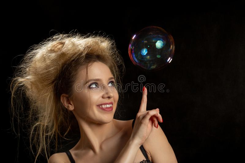 Girl with soap bubbles. Girl plays with big soap bubbles on black background stock photos