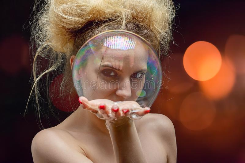 Girl with soap bubbles. Girl plays with big soap bubbles on black background with lights royalty free stock photo