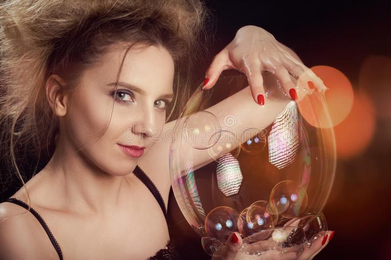 Girl with soap bubbles. Girl plays with big soap bubbles on black background with lights stock photos