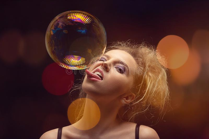 Girl with soap bubbles. Girl plays with big soap bubbles on black background with lights royalty free stock photos
