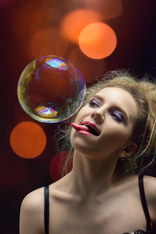Girl with soap bubbles. Girl plays with big soap bubbles on black background with lights royalty free stock photography