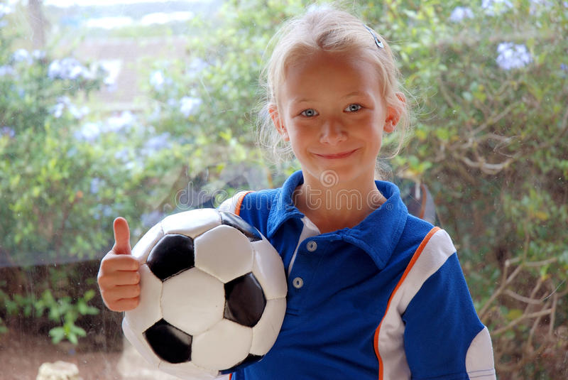 Girl with soccer ball. A cute little Caucasian white football girl holding her thumb up with her soccer ball in her arms royalty free stock image