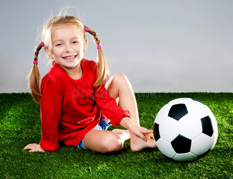Girl with soccer ball in boots. Little girl with soccer ball in boots on a green lawn royalty free stock images
