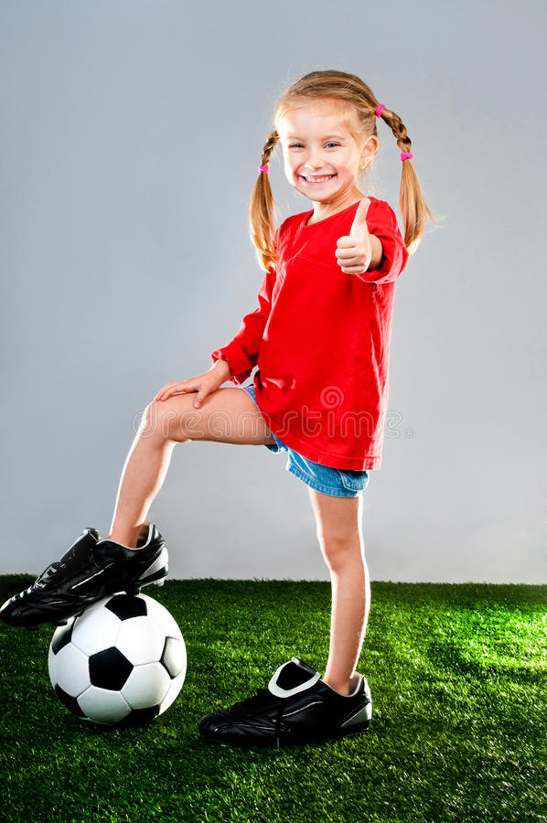 Girl with soccer ball in boots. Little girl with soccer ball in boots on a green lawn royalty free stock photography