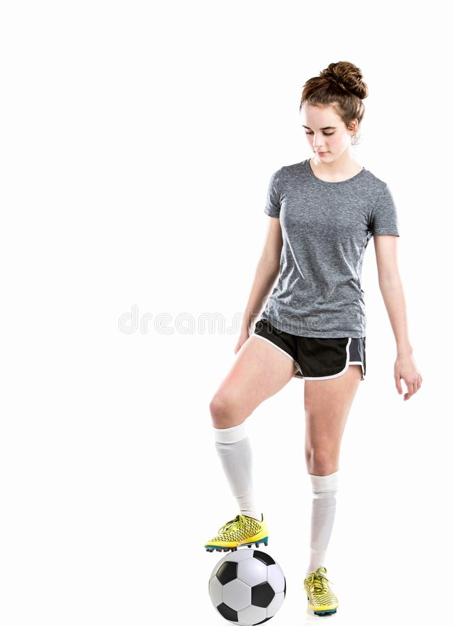 Girl with soccer ball wearing athletic clothing including soccer shoes. royalty free stock photo