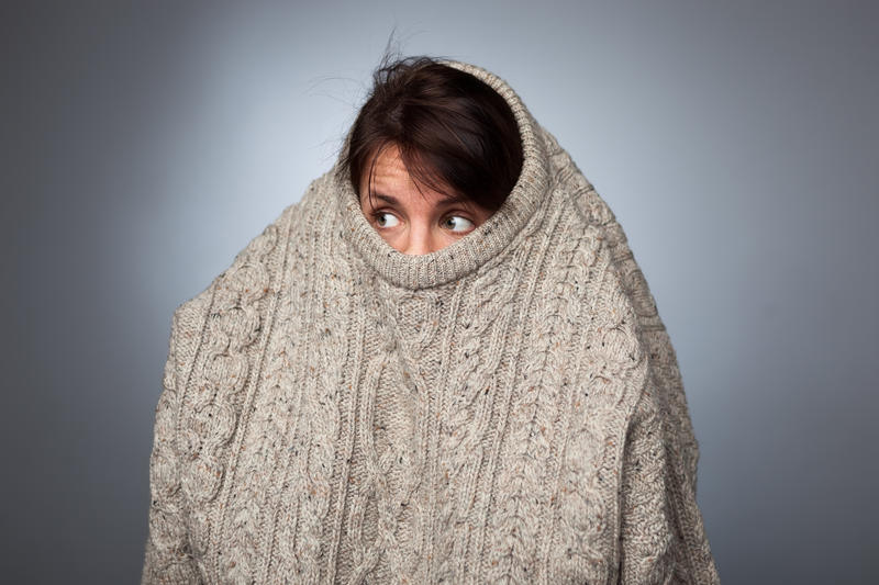 A girl with a social phobia hides her face in a sweater. royalty free stock photography