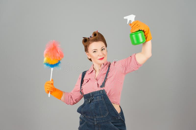 Girl with soft colorful duster and green spray bottle on grey background. Denim girl in orange gloves with brunette curls stock images