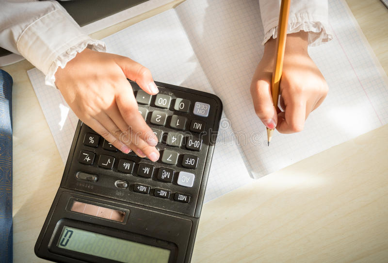 Girl solving maths task on calculator stock image