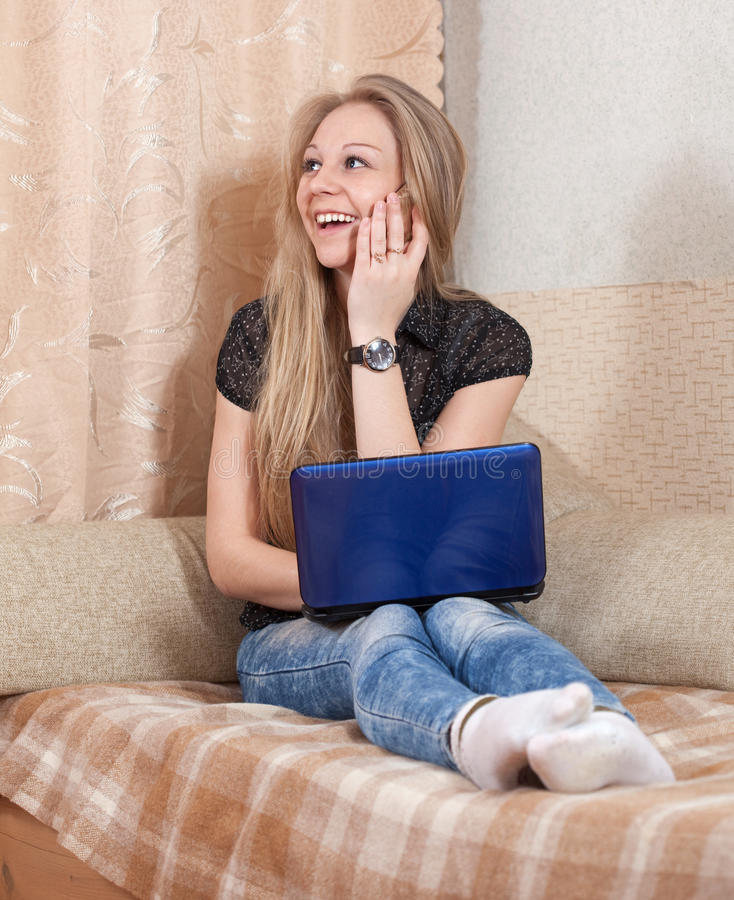 Girl speaks by mobile and uses laptop stock images