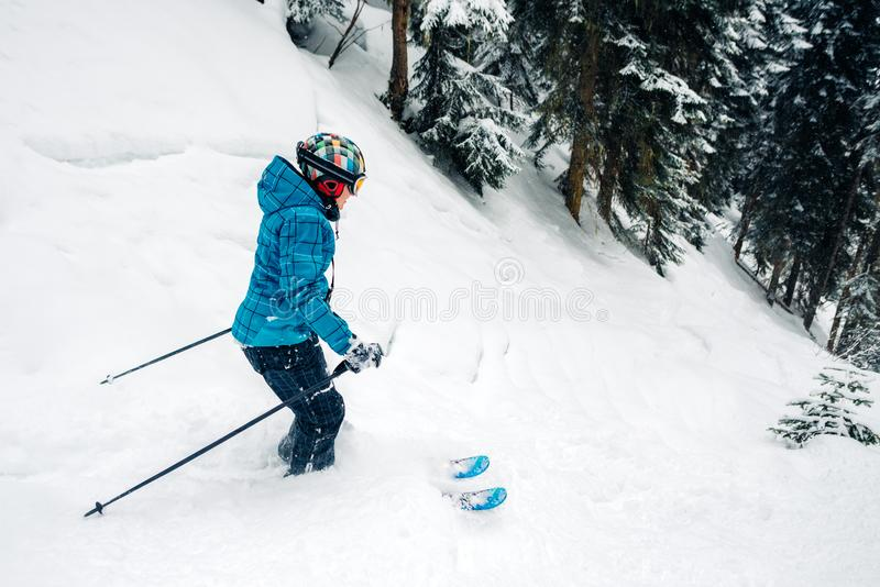 Girl with special ski equipment is riding and jumping very fast in the mountain forest royalty free stock image