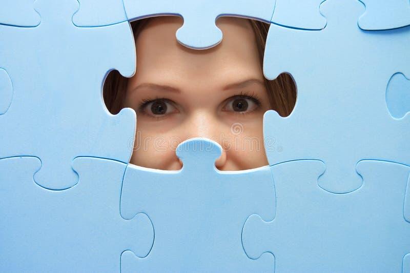 The girl spies through a blue puzzle stock photos