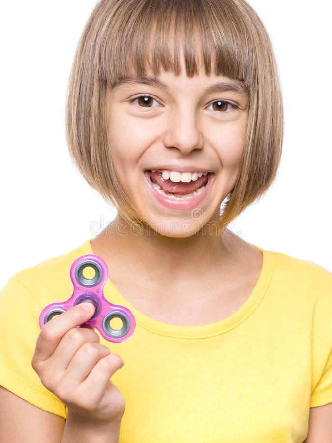 Girl with spinner. Young girl holding popular fidget spinner toy - close up portrait. Happy smiling child playing with Spinner, isolated on white background royalty free stock image