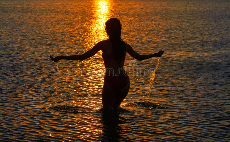 Girl silhouette at beach sunset open arms stock image
