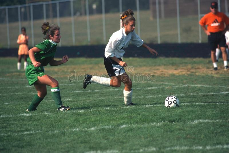 A girl`splaying in a girls soccer game royalty free stock images