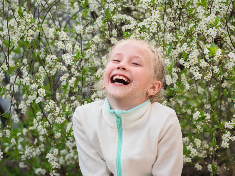 A girl in a sports jacket laughs merrily in a spring cherry Park. Portrait of a girl on a background of cherry blossoms royalty free stock photo