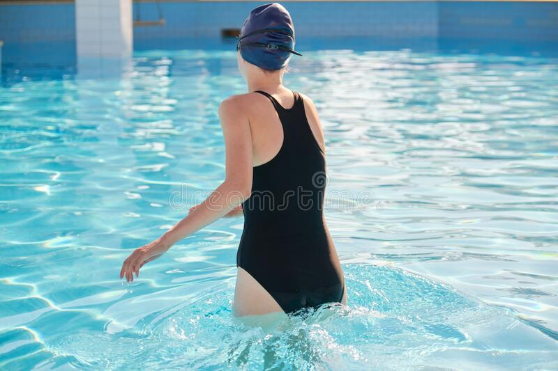 Girl in sports swimsuit and swimming cap entering the outdoor pool stock image