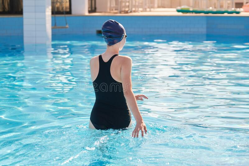 Girl in sports swimsuit and swimming cap entering the outdoor pool royalty free stock photo