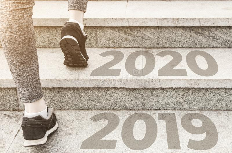 Girl in sports uniform running around. Healthy way of life, an infused figure. sneakers close-up, finish 20189 Start to new year. 2020, plans, goals, objectives stock photography