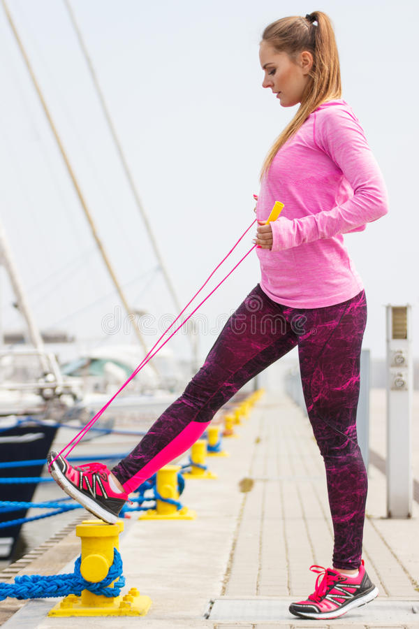 Girl in sports wear exercising with jumping rope in seaport, healthy active lifestyle royalty free stock photography
