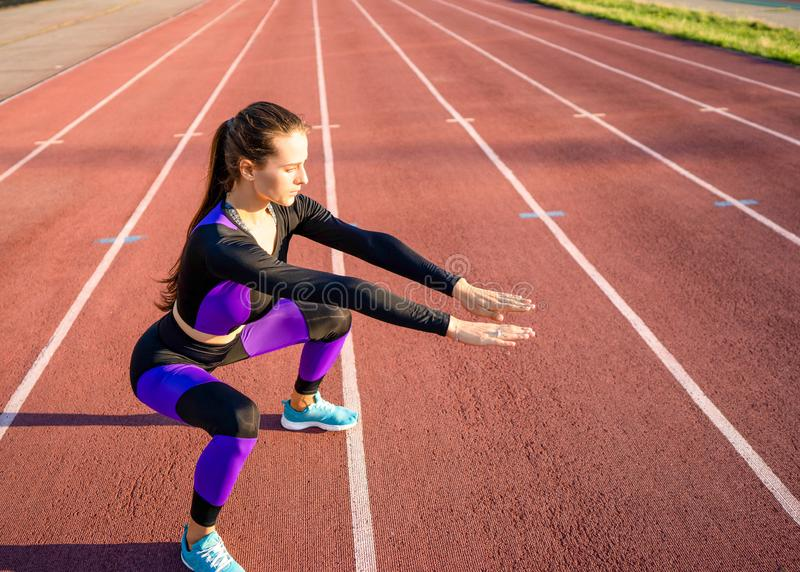 Girl sportsman crossfit and run at sunset in the stadium.  stock image