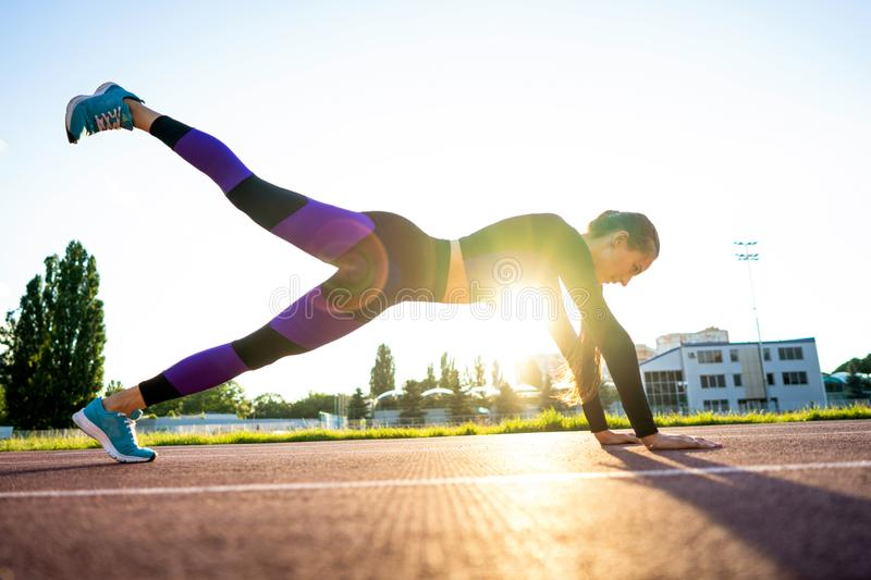 Girl sportsman crossfit and run at sunset in the stadium.  stock images