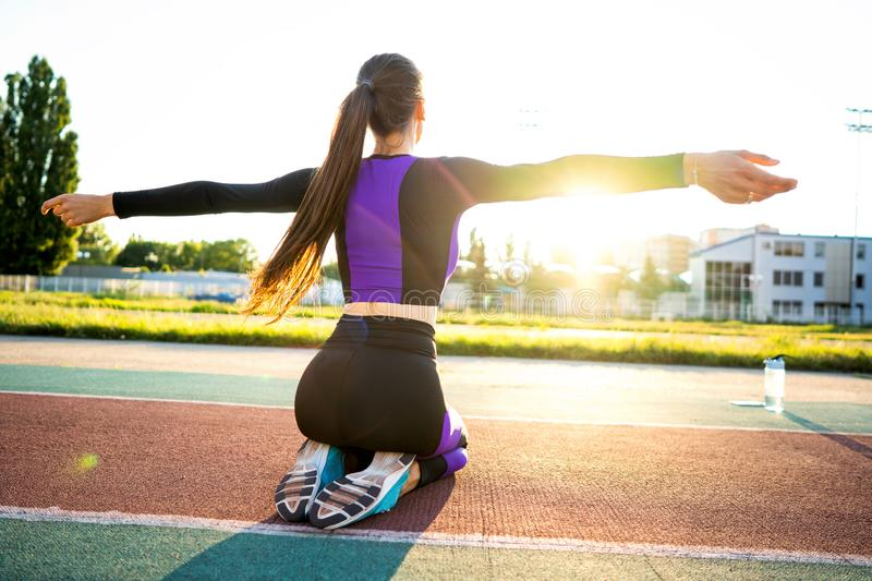 Girl sportsman crossfit and run at sunset in the stadium.  royalty free stock photos